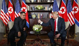 U.S. President Donald Trump, right, meets with North Korean leader Kim Jong Un on Sentosa Island in Singapore on June 12, 2018. (AP Photo/Evan Vucci)