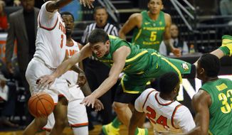 Oregon guard Payton Pritchard is fouled by Florida A&M forward Ifeanyi Umezuirika (24) as Florida A&M guard MJ Randolph (3) helps out on defense during an NCAA college basketball game, Tuesday, Dec. 18, 2018 in Eugene, Ore. (Andy Nelson/The Register-Guard via AP)