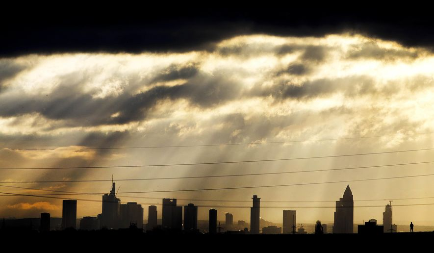 Sun rays fall through the clouds over the banking district as a runner passes by in Frankfurt, Germany, Tuesday, Dec. 11, 2018. (AP Photo/Michael Probst)