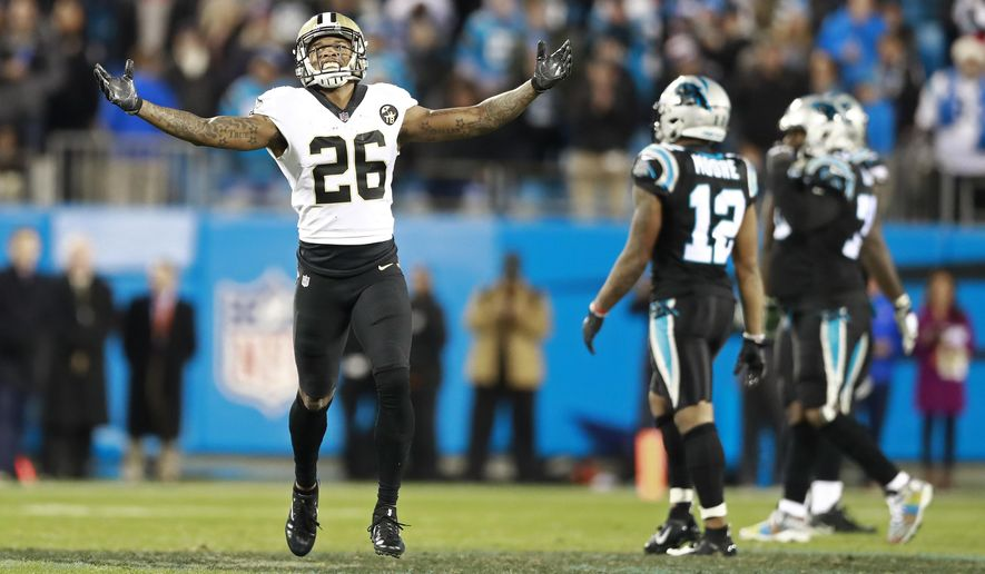 New Orleans Saints' P.J. Williams (26) celebrates as Carolina Panthers' D.J. Moore (12) walks off the field after an NFL football game in Charlotte, N.C., Monday, Dec. 17, 2018. (AP Photo/Jason E. Miczek)