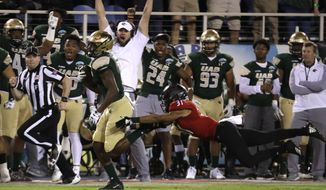 Northern Illinois wide receiver Xavier Ubosi, left, avoids a tackle by UAB safety Kyle Harrell (31) on his way to scoring a touchdown during the first half of the Boca Raton Bowl NCAA college football game, Tuesday, Dec. 18, 2018, in Boca Raton, Fla. (AP Photo/Lynne Sladky)