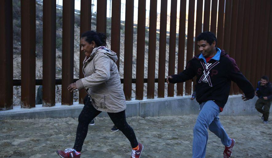 Honduran migrants run away from Border Patrol agents as they try to cross over the U.S. border wall to San Diego, California, from Tijuana, Mexico, Saturday, Dec. 15, 2018. (AP Photo/Moises Castillo)