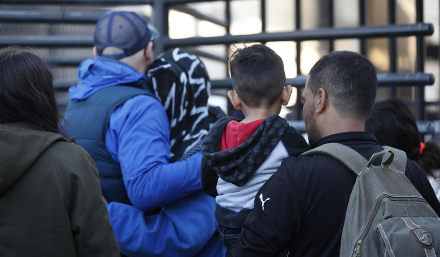 Honduran asylum seekers enter the U.S. at San Diego's Otay Mesa port of entry, as seen from Tijuana, Mexico, Tuesday, Dec. 18, 2018. Six Honduran asylum seekers spent a chilly night camped out on a tiny patch of U.S. soil at a San Diego border crossing seeking to have their claims processed. (AP Photo/Moises Castillo)