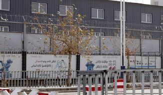 """In this Wednesday, Dec. 5, 2018, photo, two layers of barbed wire fencing ring the """"Hotan City apparel employment training base"""" where Hetian Taida has a factory in Hotan in western China's Xinjiang region. (AP Photo/Ng Han Guan)"""