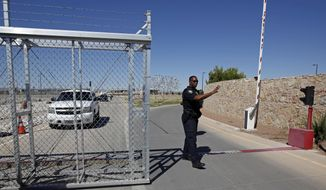 FILE - In this June 21, 2018, file photo, an agent with the Department of Homeland Security controls access to a holding facility for immigrant children in Tornillo, Texas. The Trump administration is reversing a policy that required fingerprinting for all adults living in a household where a migrant child would live. Parents and other sponsors have said the fingerprinting rule had slowed placement of children in homes, in part because some members of the household were afraid to be fingerprinted. (AP Photo/Andres Leighton, File)