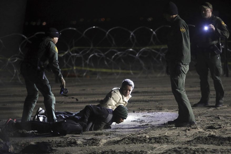 In this Nov. 30, 2018, file photo, U.S. Border Patrol officers detain Honduran migrants after they walked onto U.S. territory from Tijuana, Mexico. (AP Photo/Felix Marquez, File)