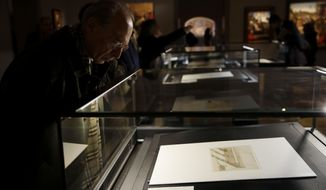 """Visitors attend the press presentation of the 'Secrets of the Codex Atlanticus. Leonardo at the Ambrosiana"""" exhibition, at the Ambrosiana Library in Milan, Italy, Tuesday, Dec. 18, 2018. The Leonardo year at the Ambrosiana opens on 18 December 2018 with an exhibition in two parts, each lasting three months, which will present a total of 46 sheets, chosen from among the most famous and important of the Codex Atlanticus, the true Leonardo treasure at the Ambrosiana, retracing the career of the artist almost from beginning to end, from his early years in Florentine until his last years in France in the service of Francis I. The first part of the exhibition from 18 December 2018 to March 17, 2019, opens with Leonardo's drawings specifically related to the city of Milan. (AP Photo/Luca Bruno)"""