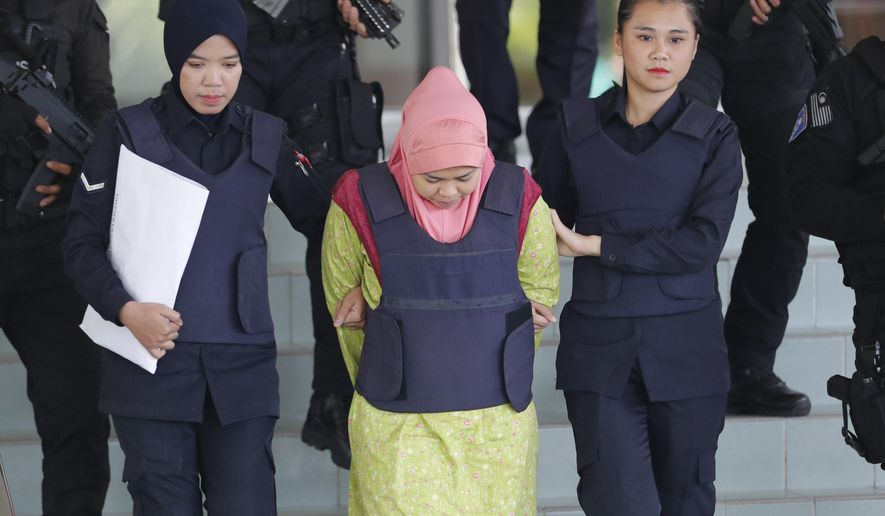 Indonesian Siti Aisyah, center, escorted by police, leaves Shah Alam High Court after a court hearing in Shah Alam, Malaysia on Tuesday, Dec. 18, 2018. Siti and Vietnamese Doan Thi Huong, charged with murdering North Korea leader's half brother Kim Jong Nam, were back in Malaysia court for a procedural hearing. (AP Photo/Vincent Thian)