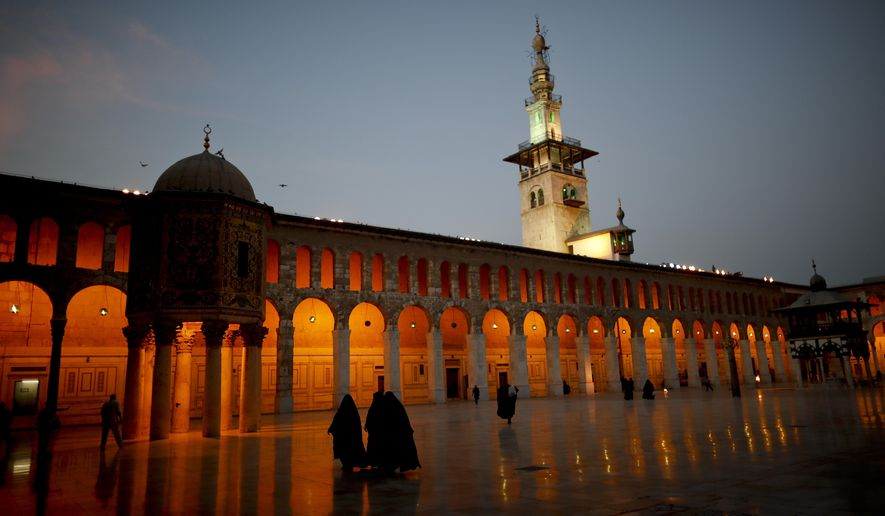 Muslim women walk in the courtyard of the 7th century Umayyad Mosque in Damascus, Syria, Wednesday, Oct. 3, 2018. (AP Photo/Hassan Ammar)