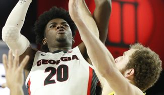 Georgia forward Rayshaun Hammonds (20) takes a shot while being defended by Oakland center Brad Brechting (13) during an NCAA college basketball game in Athens, Ga., on Tuesday, Dec. 18, 2018. (Joshua L. Jones/Athens Banner-Herald via AP)