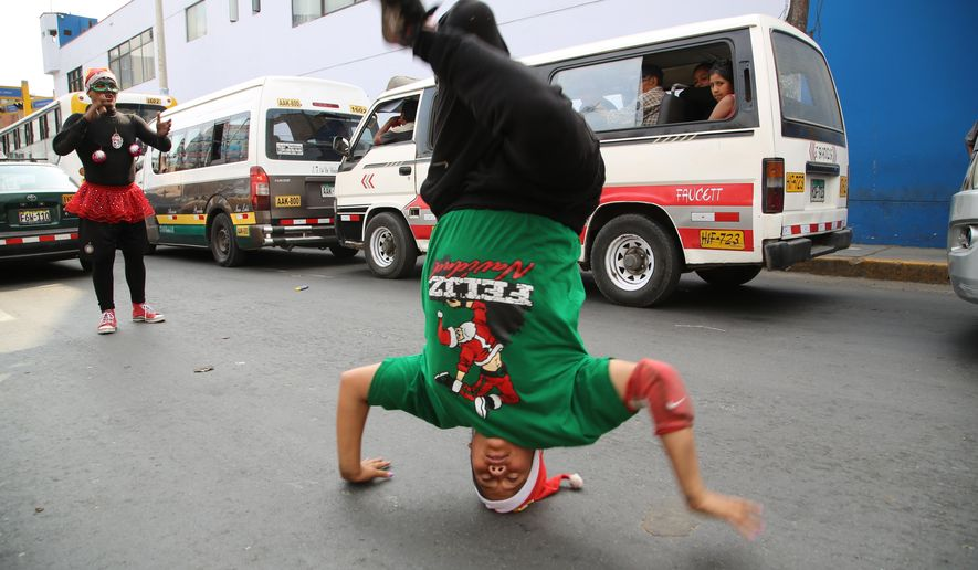 In this Dec. 12, 2018 photo, Venezuelan Karin Rojas balances on her head as she breakdances with Angel Fernandez for tips from commuters in Lima, Peru. Rojas, 25, arrived in Lima in 2016, leaving behind her mountainous home in the Venezuelan state of Merida, where she ran a break dancing collective with her husband. (AP Photo/Cesar Olmos)