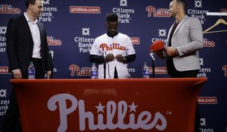 Philadelphia Phillies new outfielder Andrew McCutchen, center, accompanied by general manager Matt Klentak, left, and manager Gabe Kapler, puts on his uniform during a news conference in Philadelphia, Tuesday, Dec. 18, 2018. McCutchen and the Philadelphia Phillies finalized a back-loaded $50 million, three-year contract last week, a deal that includes a team option for 2022. (AP Photo/Matt Rourke)