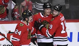 Chicago Blackhawks defenseman Gustav Forsling, center, celebrates his goal against the Nashville Predators with center Dominik Kahun (24) and center Jonathan Toews (19) during the second period of an NHL hockey game Tuesday, Dec. 18, 2018, in Chicago. (AP Photo/David Banks)