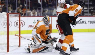 Philadelphia Flyers' Carter Hart, left, blocks a shot as Detroit Red Wings' Justin Abdelkader, center, and Travis Sanheim look for the rebound during the first period of an NHL hockey game, Tuesday, Dec. 18, 2018, in Philadelphia. (AP Photo/Matt Slocum)