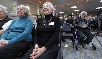 Senior housing resident Marjorie Portin, center, looks on with other seniors during a news conference announcing that Seattle will invest more than $75 million on affordable-housing units in the next year. Mayor Jenny Durkan says the investment puts the city on target to make available nearly 4,000 new homes by 2022. (AP Photo/Elaine Thompson)