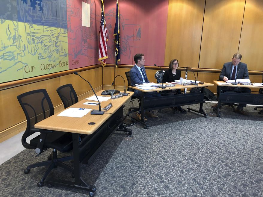 Gov. Kate Brown, middle, speaks on Tuesday, Dec. 18, 2018, at an Oregon State Land Board meeting in Salem, Ore. Secretary of State Dennis Richardson's desk sits empty at left with him attending via speakerphone. A day earlier, Richardson, who is being treated for brain cancer, reversed his decision to temporarily leave the state land board. The third board member, state Treasurer Tobias Read, is on the right. Next to Brown is Brown's natural resources policy manager, Jason Miner. (AP Photo/Andrew Selsky)