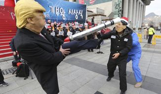 A protester, left, wearing a mask of U.S. President Donald Trump kicks his fellow protester wearing a mask of North Korean leader Kim Jong Un during a rally to denounce policies of South Korean President Moon Jae-in on North Korea in Seoul, South Korea, Tuesday, Dec. 18, 2018. Kim's return visit to Seoul appears unlikely to take place this month, a senior South Korean official said last week. (AP Photo/Ahn Young-joon)