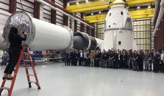 SpaceX employees gather for a group photo in front of the Dragon capsule at a SpaceX hangar in Cape Canaveral, Fla., Tuesday, Dec. 18, 2018. The capsule is being readied for a January test flight, minus a crew. (AP Photo/Marcia Dunn)