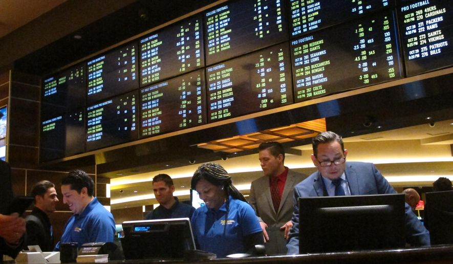 This Oct. 25, 2018 photo shows employees at the new sports book at the Tropicana casino in Atlantic City N.J., preparing to take bets moments before it opened. On Dec. 18, 2018, Canadian firm theScore announced it will enter New Jersey's sports betting market next year, and the NBA and FanDuel announced a gambling agreement. (AP Photo/Wayne Parry) ** FILE **
