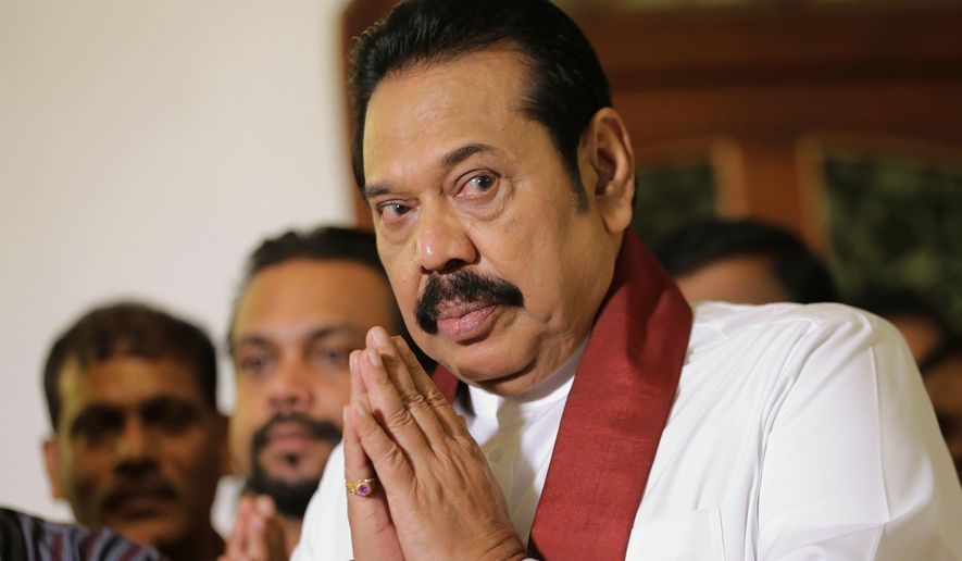 FILE - In this Saturday, Dec. 15, 2018 file photo, Sri Lanka's disputed prime minister Mahinda Rajapaksa folds his hands in prayer as he is blessed by a Buddhist monk after signing his resignation paper in Colombo, Sri Lanka.  Members of Sri Lanka's Parliament on Tuesday questioned whether Rajapaksa, who recently quit as prime minister, can hold his seat after earlier relinquishing membership in the political party that he represented in the last election. (AP Photo/Eranga Jayawardena)