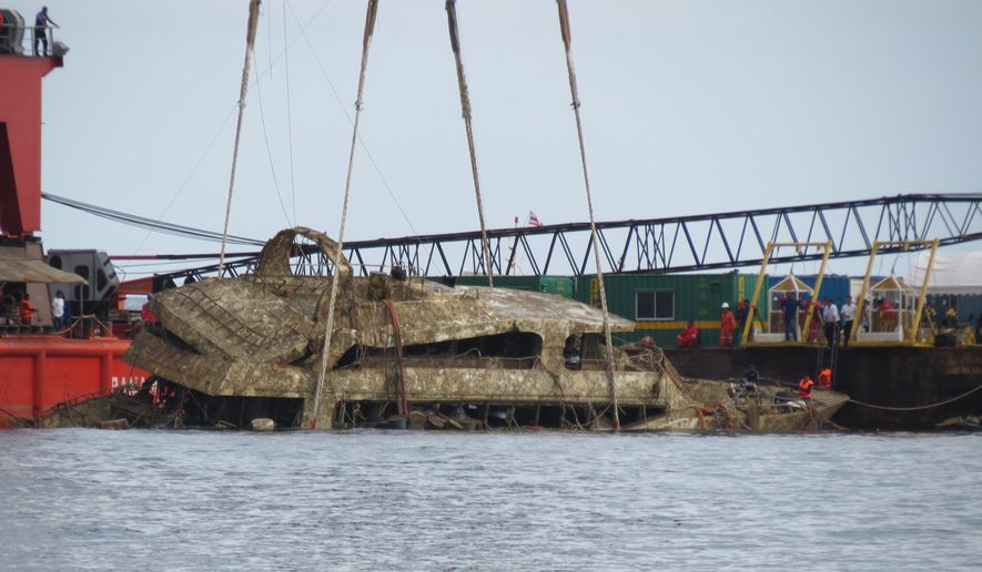 FILE - In this Nov. 17, 2018, file photo, a crane boat raises the tour boat named the Pheonix from the sea floor in Phuket, Thailand, after sinking over four months ago in rough weather.  Police in Thailand say their investigations found that the boat that sank in rough weather in July, killing 47 Chinese tourists, didn't meet regulatory standards. (AP Photo, File)