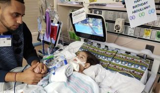 This recent but undated photo, released Monday, Dec. 17, 2018 by the Council on American-Islamic Relations in Sacramento, Calif., shows Ali Hassan with his dying 2-year-old son Abdullah in a Sacramento hospital. The boy's Yemeni mother, blocked by the Trump administration's travel ban, has won her fight for a waiver that would allow her to travel to California to see her son. Basim Elkarra of the Council on American-Islamic Relations in Sacramento said Shaima Swileh was granted a visa Tuesday, Dec. 18, 2018, and will be flying to San Francisco on Wednesday, Dec. 19, 2018. (Council on American-Islamic Relations via AP)