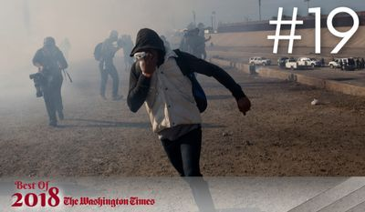 BEST OF 2018 - A migrant runs from tear gas launched by U.S. agents, amid members of the press covering the Mexico-U.S. border, after a group of migrants got past Mexican police at the Chaparral crossing in Tijuana, Mexico, Sunday, Nov. 25, 2018. The mayor of Tijuana has declared a humanitarian crisis in his border city and says that he has asked the United Nations for aid to deal with the approximately 5,000 Central American migrants who have arrived in the city.  (AP Photo/Rodrigo Abd)