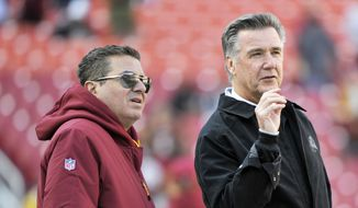 Washington Redskins owner Dan Snyder (left) and president Bruce Allen (right) talk on the field prior to an NFL football game between the Dallas Cowboys and Washington Redskins, Sunday, Oct. 21, 2018, in Landover, Md. (AP Photo/Mark Tenally) **FILE**