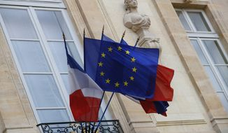 """European and French flags are flapping at the Elysee Palace in Paris, Monday, Dec. 10, 2018 during a meeting with French President Emmanuel Macron and local, national political leaders, unions, business leaders and others to hear their concerns after four weeks of protests. French President Emmanuel Macron is preparing to speak to the nation at last after increasingly violent """"yellow vest"""" protests against his leadership. (AP Photo/Francois Mori)"""