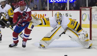 Washington Capitals center Nicklas Backstrom (19), from Sweden, goes for the puck as Pittsburgh Penguins goaltender Matt Murray (30) defends in the second period of an NHL hockey game, Wednesday, Dec. 19, 2018, in Washington. (AP Photo/Alex Brandon)