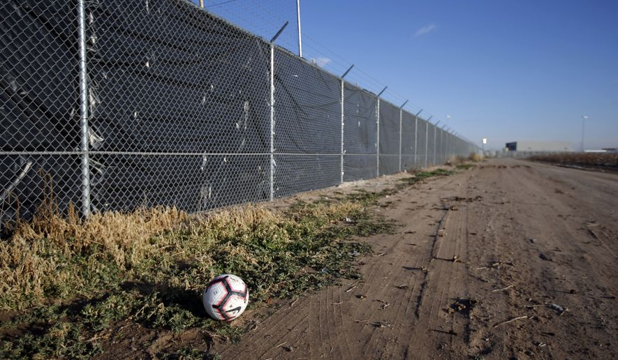 A soccer ball rest next to the tarp covered fence outside the Tornillo detention camp for migrants in Tornillo, Texas, Thursday Dec. 13, 2018. The Trump administration announced in June 2018 that it would open the temporary shelter for up to 360 migrant children in this isolated corner of the Texas desert. Less than six months later, the facility has expanded into a detention camp holding thousands of teenagers, showing every sign of becoming more permanent. (AP Photo/Andres Leighton)