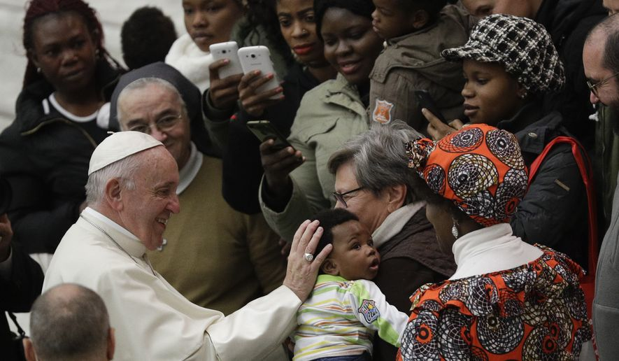 Pope Francis caresses a child as he meets with faithful on the occasion of the weekly general audience, at the Vatican, Wednesday, Dec. 19, 2018. (AP Photo/Gregorio Borgia)