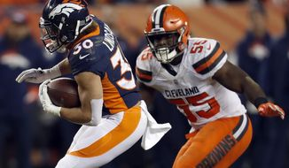 Denver Broncos running back Phillip Lindsay (30) tries to elude Cleveland Browns outside linebacker Genard Avery (55) during the first half of an NFL football game, Saturday, Dec. 15, 2018, in Denver. (AP Photo/David Zalubowski)