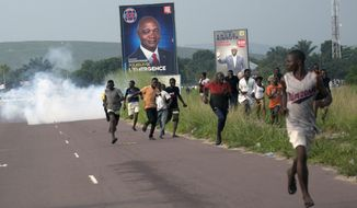 Supporters of opposition candidate Martin Fayulu run from tear gas fired by police in Snele, Democratic Republic of the Congo, Wednesday Dec. 19, 2018. Days before Congo's elections, the Kinshasa's governor banned campaign rallies in the capital city, citing security concerns. The capital's governor Andre Kimbuta on Wednesday cancelled all political rallies in the city for the 21 candidates vying for the presidency in the Dec. 23 elections. (AP Photo/Jerome Delay)