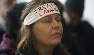 FILE - In this Nov. 19, 2018 file photo, Nancy Beaulieu, a member of the Leech Lake Tribe, attends a Public Utilities Commission meeting in St. Paul, to oppose Enbridge's Line 3 pipeline. Opponents of Enbridge Energy's plan to replace its aging Line 3 crude oil pipeline across northern Minnesota have filed appeals to challenge the state Public Utilities Commission's approval of the project. Environmental and tribal groups filed initial notices Wednesday with the Minnesota Court of Appeals against the commission's decision to grant a certificate of need for the project. Canada-based Enbridge says it believes the courts will reaffirm the project's approval. (Richard Tsong-Taatarii/Star Tribune via AP, File)