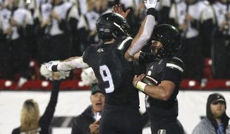 Ohio wide receiver Andrew Meyer (9) celebrates a touchdown by Ohio quarterback Nathan Rourke (12) in the first half of the Frisco Bowl NCAA college football game against San Diego State, Wednesday, Dec. 19, 2018, in Frisco, Texas. (AP Photo/Richard W. Rodriguez)