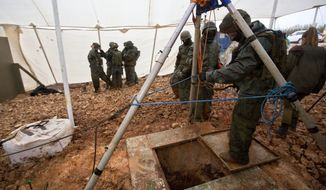 "Israeli soldiers stand around the opening of a hole that leads to a tunnel that the army says crosses from Lebanon to Israel, near Metula, Wednesday, Dec. 19, 2018. Israel's prime minister Wednesday called on the U.N. Security Council to condemn ""wanton acts of aggression"" by the Lebanese militant group Hezbollah, designate it a terrorist organization and heighten sanctions on it over attack tunnels it has dug into Israel. (AP Photo/Sebastian Scheiner)"