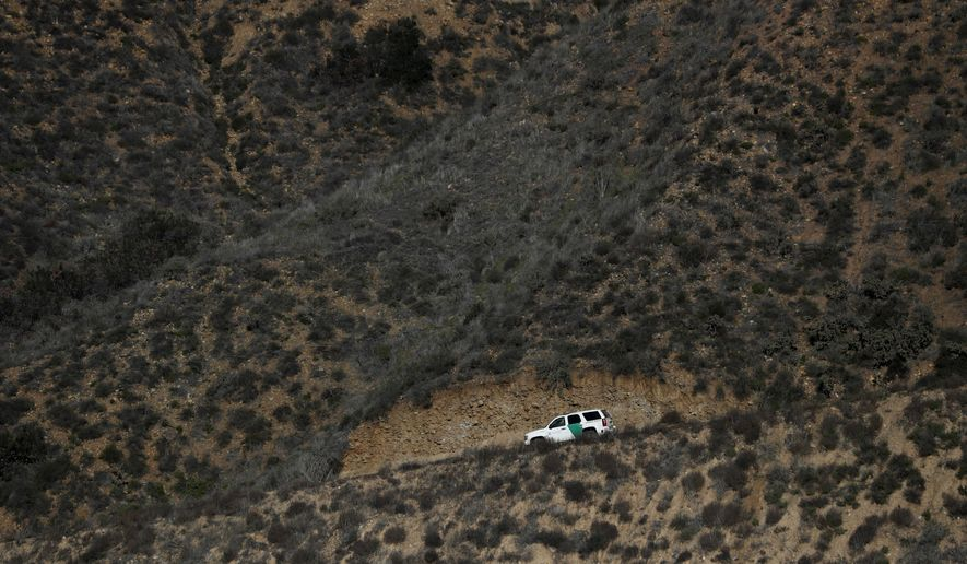 A U.S. Border Patrol vehicle moves along a road in San Diego across the U.S. border wall and seen from Tijuana, Mexico, Wednesday, Dec. 19, 2018. (AP Photo/Moises Castillo) ** FILE **
