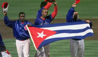 In this Monday, May 3, 1999 file photo, members of the Cuban baseball team carry their country's flag onto the field after a baseball game against the Baltimore Orioles at Camden Yards in Baltimore. . (AP Photo/Nick Wass, File) **FILE**
