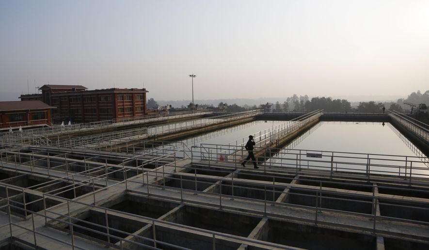 A Nepalese security guard walks at the construction site of Melamchi water project in Kathmandu, Nepal, Wednesday, Dec. 19, 2018.  The government of Nepal has stopped Italian contractors from leaving the Himalayan country in an effort to complete a critical but much delayed water supply project for the capital city. The Italians have been working for the past four years but the Melamchi project is nearly two decades old and supposed to bring drinking water to Kathmandu, where households have water for only two hours every five days. (AP Photo/Niranjan Shrestha)