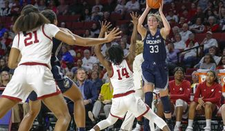 Connecticut guard/forward Katie Lou Samuelson (33) looks to pass the ball as Oklahoma guard Shaina Pellington (14) defends during the first half of an NCAA college basketball game in Norman, Okla., Wednesday, Dec. 19, 2018. (AP Photo/Alonzo Adams)