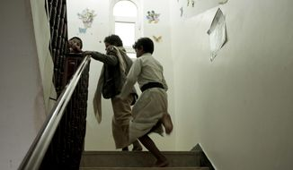 "Boys run up the stairs at a rehabilitation center for former child soldiers in Marib, Yemen, in this July 25, 2018, photo. Boys come to center traumatized and mistrustful from their experiences on the battlefield. On his first day at the center, one said he was terrified, unsure what they would do to him. ""But then I saw the teachers and they gave me a room to stay in. I felt good after that."" (AP Photo/Nariman El-Mofty)"