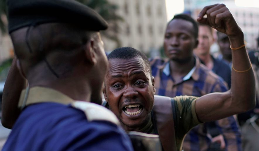 Fiston Adumba, 32, an opposition supporter, reacts to Corneille Nangaa announcing the postponement of the elections, in Kinshasa, Democratic Republic of the Congo, Thursday Dec. 20, 2018. Congo's electoral commission has delayed the country's long-awaited presidential election until Dec. 30, citing problems caused by a recent fire that destroyed 80 percent of the voting machines in the capital. (AP Photo/Jerome Delay)