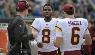 Washington Redskins passing game coordinator Kevin O'Connell, left, talks with quarterback Josh Johnson (8) and quarterback Mark Sanchez (6) on the sideline during the first half of an NFL football game against the Jacksonville Jaguars Sunday, Dec. 16, 2018, in Jacksonville, Fla. (AP Photo/Phelan M. Ebenhack)