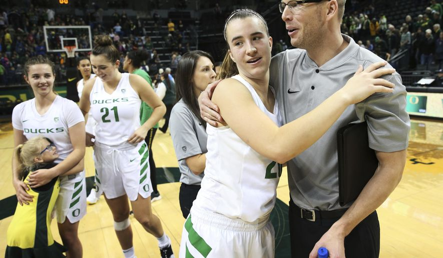 Oregon's Sabrina Ionescu, center left, gets a hug from acting head coach Mark Campbell, right, after their win over Air Force in an NCAA college basketball game, Thursday Dec. 20, 2018, in Eugene, Ore. Head coach Kelly Graves had to sit out the game as part of an NCAA suspension. (Chris Pietsch/The Register-Guard via AP)