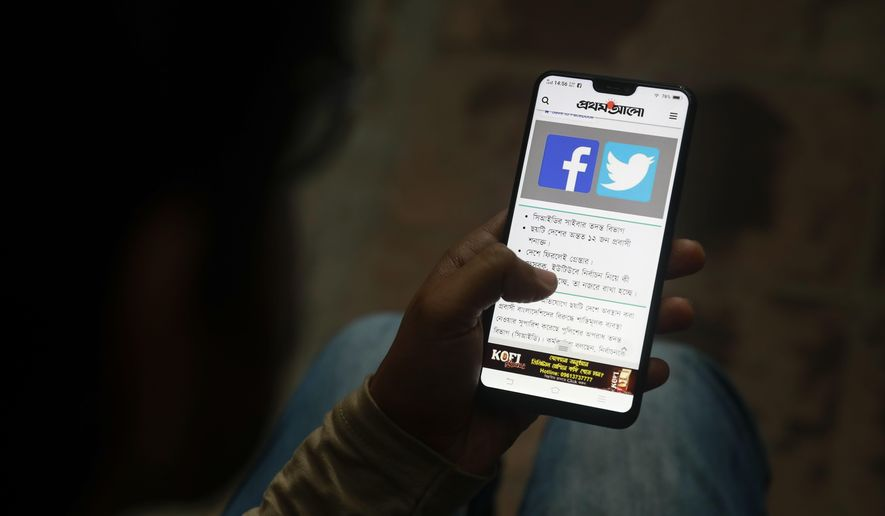 A Bangladeshi reads a news report that makes mention of Facebook along with other social networking service, on his mobile phone in Dhaka, Bangladesh, Thursday, Dec. 20, 2018. Facebook is shutting down a series of fake news sites spreading false information about the Bangladesh opposition days before national elections, a top security official with the global social media platform said Thursday. The sites _ nine Facebook pages designed to mimic legitimate news outlets, as well as six fake personal accounts spreading anti-opposition propaganda _ were created by Bangladeshis associated with the government, Nathaniel Gleicher, Facebook's head of cybersecurity policy, told the AP in an exclusive interview. (AP Photo)