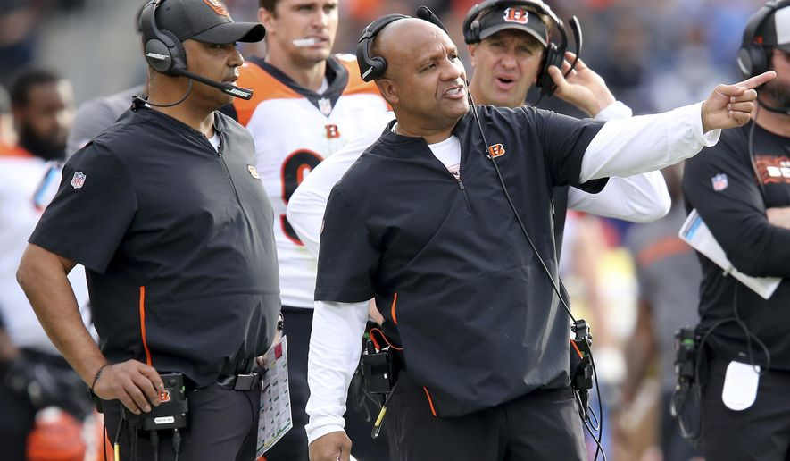 FILE - In this Dec. 9, 2018, file photo, Cincinnati Bengals special assistant to the head coach Hue Jackson, right, points something out to head coach Marvin Lewis during the second quarter of an NFL football game against the Los Angeles Chargers in Carson, Calif. Jackson returns to Cleveland on Sunday, for the first time since he was fired by the Browns on Oct. 29. (Kareem Elgazzar/The Cincinnati Enquirer via AP, File)