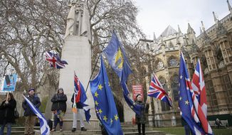 Anti-Brexit demonstrators wave flags outside the houses of Parliament in London, Wednesday Dec. 19, 2018. (AP Photo/Tim Ireland)