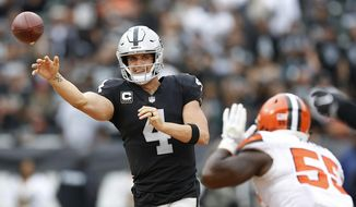 FILE - In this Sunday, Sept. 30, 2018, file photo, Oakland Raiders quarterback Derek Carr (4) passes against Cleveland Browns linebacker Genard Avery (55) during overtime of an NFL football game in Oakland, Calif. Carr is the first player in four years to get sacked at least three times in seven consecutive games but remains on pace for his first career 4,000-yard season. (AP Photo/D. Ross Cameron) ** FILE **
