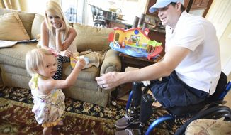 FILE--In this AprIl 1, 2015, file photo, retired Air Force Airman Brian Kolfage, right, gives a piece of cheese to his one-year-old daughter Paris Kolfage as his wife Ashley Kolfage looks on at their recently rented home in Sandestin, Fla. Kolfage, a triple-amputee who lost his limbs serving in Iraq in the U.S. Air Force, started a GoFundMe page to help fund construction of President Donald Trump's border wall has already raised millions of dollars.(Nick Tomecek/Northwest Florida Daily News via AP, file)